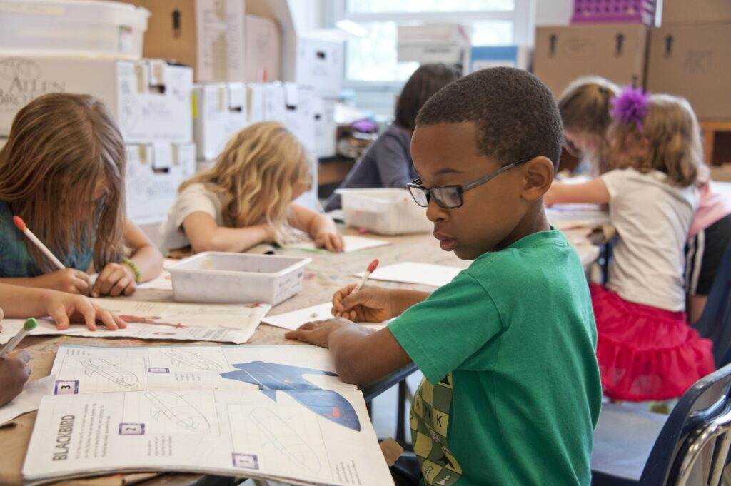 little black boy writing in a workbook in a busy classroom
