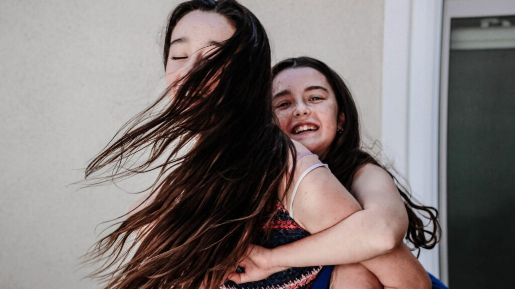 Two young girls playing piggyback