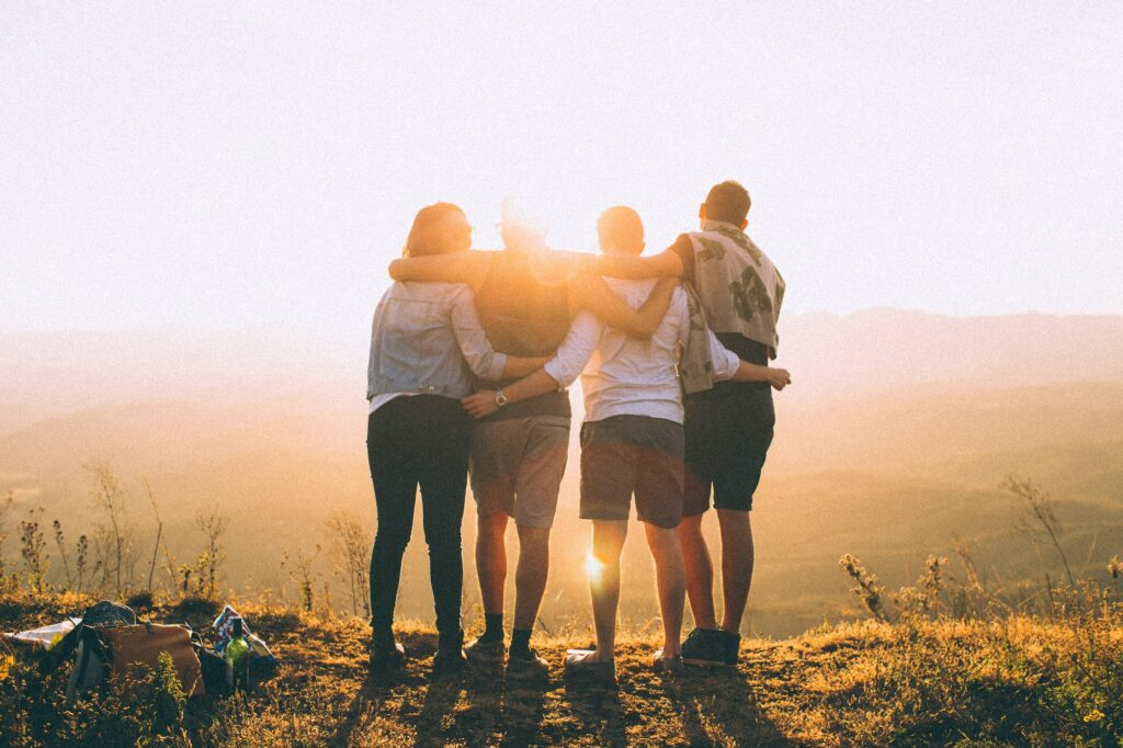 group of four friends with their arms around each other looking out over a sunny view